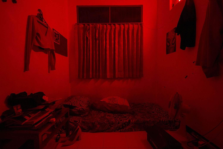 Suasana kamar kos Alen (21) sepi pengunjung semenjak COVID-19 menyebar luas di Indonesia. Pembatasan Sosial Berskala Besar (PSBB) membuat Alen selaku Pekerja Seks  sangat bimbang karena tidak bisa menerima tamu secara langsung.
