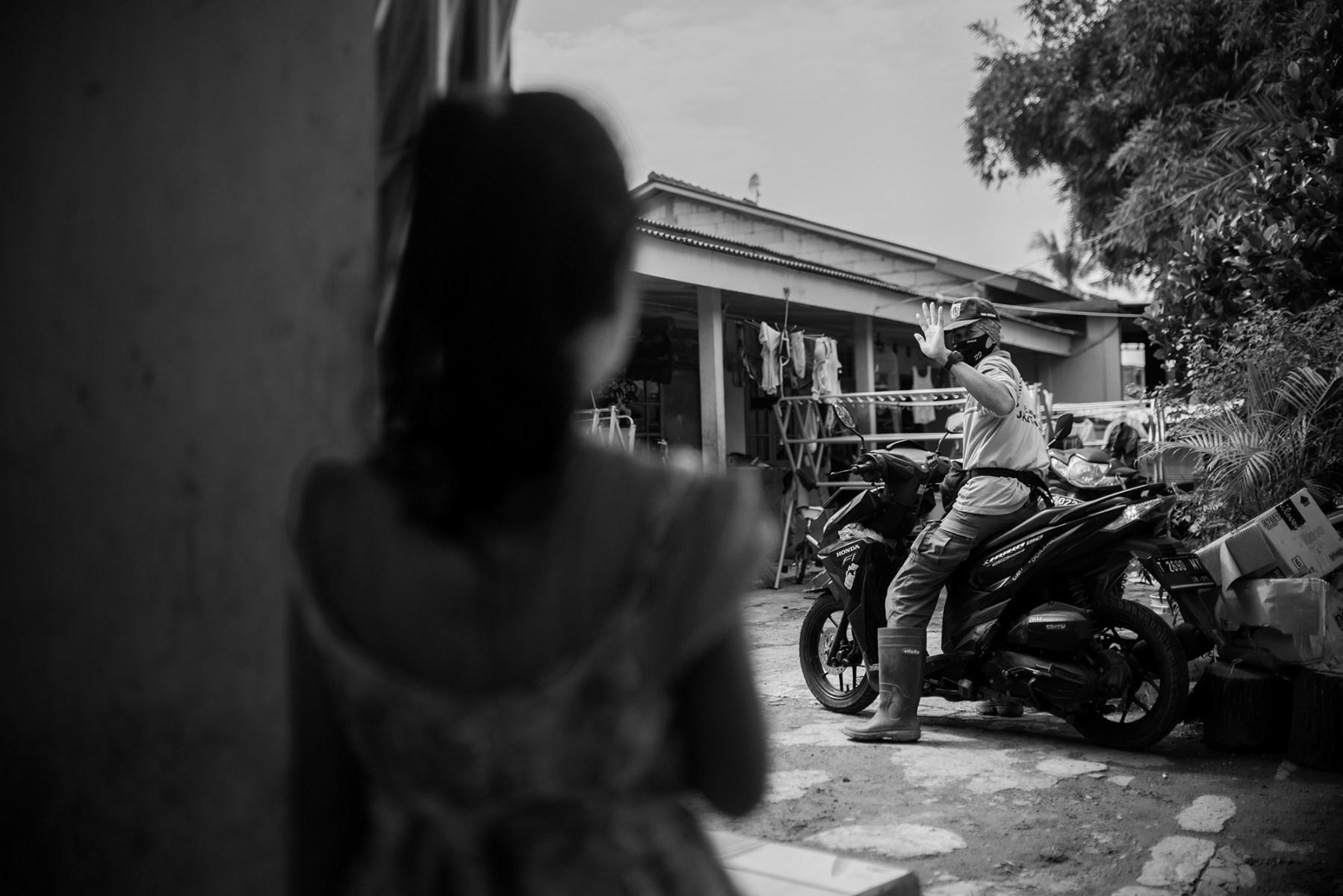 Nadi Bin Eji Alias Amang melambaikan tangan ke anaknya saat akan berangkat kerja ke Tempat Pemakaman Umum di  Pondok Ranggon, Jakarta Timur.