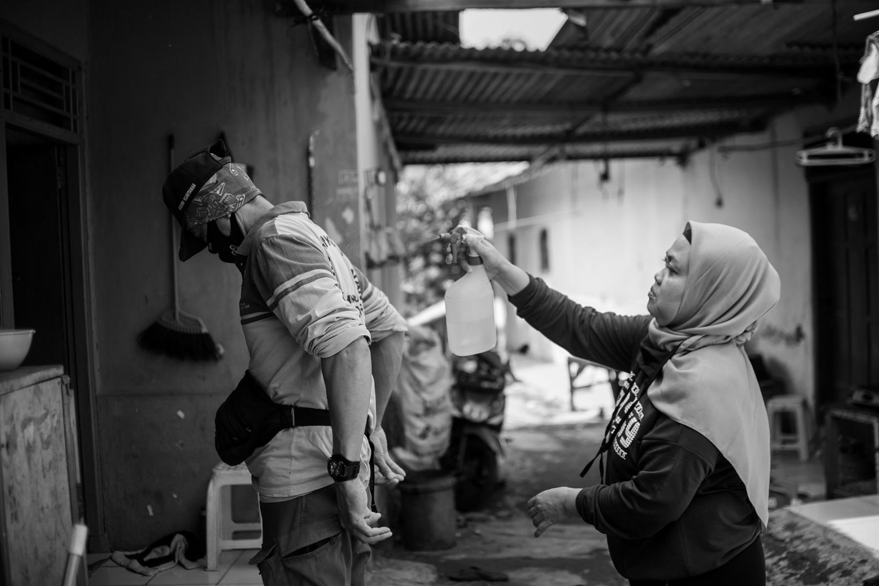Onah (42) Istri Nadi Bin Eji Alias Amang menyemprotkan cairan disinfektan saat akan masuk rumahnya di kawasan Pondok Ranggon, Jakarta Timur.