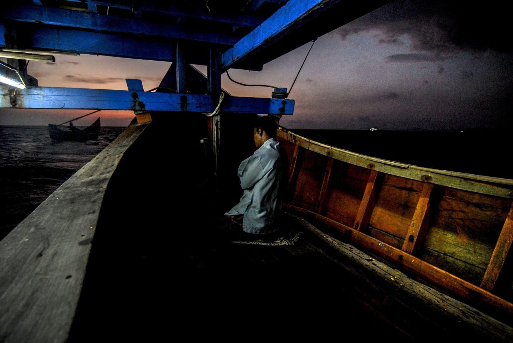 Zainal (53), melaksanakan ibadah shalat maghrib di dalam kapal palong dalam perjalanan menuju laut, Jumat (13/4/2018).