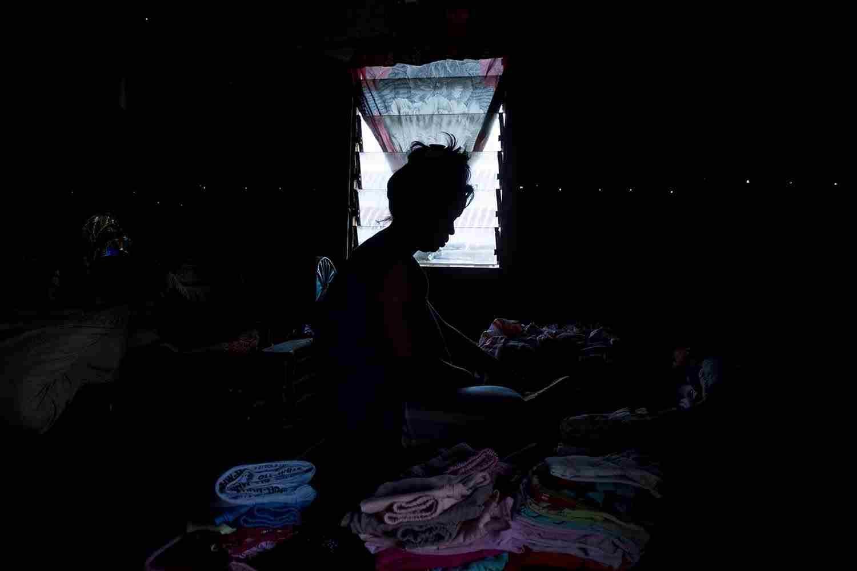 Siluet Nindra A.N saat melipat pakaian di rumahnya di Keluarahan Panampu, Kecamatan Tallo, Makassar, Jumat, (21/08/2020)