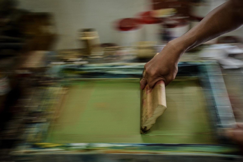 Warnadi saat mengerjakan pesanan sablon di rumahnya yang terletak di Petukangan Utara, Jakarta Selatan, Rabu (29/7). Selain bagian kaki, bentuk jari-jari tangan Warnadi turut mengalami kelainan fisik.