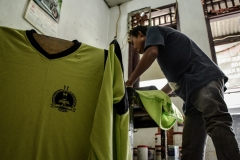 Warnadi saat menyablon seragam sekolah di rumahnya yang terletak di Petukangan Utara, Jakarta Selatan, Rabu (5/8). Kaki palsu menjadi penopang tubuhnya dalam menjalani pekerjaan.