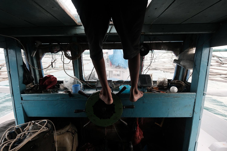 Irwan mengemudikan kapal menggunakan kaki dikarenakan susahnya jarak pandang kapal bagan saat melaut dari Tanjung Binga, Belitung, pada 27 Juli 2020. JP/Donny Fernando
