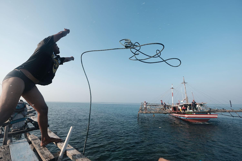 Ocang melempar tali untuk meminta bantuan kapal lain agar menarik kapalnya yang tersangkut di karang pada 8 Agustus 2020. JP/Donny Fernando